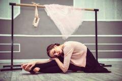 Молодая красивая грациозно балерина отдыхая в sitti класса балета Стоковая Фотография