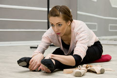 Молодая красивая грациозно балерина отдыхая в sitti класса балета Стоковые Изображения RF