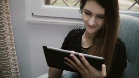 Молодая красивая девушка брюнет занимаясь серфингом интернет и используя планшет для того Привлекательная девушка отдыхая дома сток-видео
