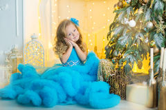 Молодая красивая девушка в голубом белом элегантном платье вечера сидя на поле около рождественской елки и настоящих моментах на  стоковые изображения rf