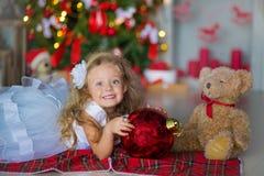 Молодая красивая девушка в голубом белом элегантном платье вечера сидя на поле около рождественской елки и настоящих моментах на  стоковые фото