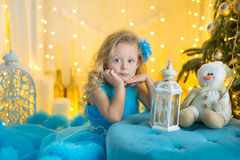 Молодая красивая девушка в голубом белом элегантном платье вечера сидя на поле около рождественской елки и настоящих моментах на  стоковое изображение rf
