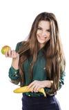 Молодая красивая девушка в зеленой блузке держа яблоко и банан и усмехаться изолят стоковые фото