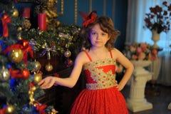 Молодая красивая девушка в красном платье на рождественской елке на рождестве Стоковые Изображения RF
