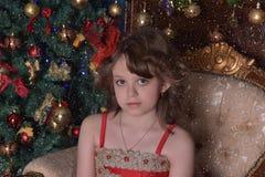 Молодая красивая девушка в красном платье на рождественской елке на рождестве Стоковое Фото