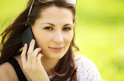 Молодая красивая девушка в парке города говорит передвижным phon Стоковое Изображение RF