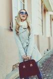 Молодая красивая девушка в стильных солнечных очках и с улицами модными города сумки стоковые фото