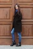 Молодая красивая девушка в черном пальто и голубом шарфе имея потеху Элегантная девушка брюнет с шикарными дополнительными длинны Стоковая Фотография