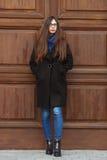 Молодая красивая девушка в черном пальто и голубом шарфе имея потеху Элегантная девушка брюнет с шикарными дополнительными длинны Стоковое Изображение RF