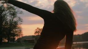 Молодая красивая девушка в черных одеждах танцуя, на береге реки, силуэт видеоматериал