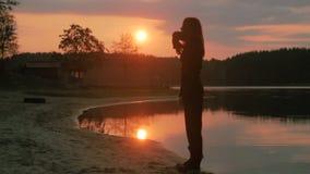 Молодая красивая девушка в черных одеждах танцуя, на береге реки, силуэт сток-видео