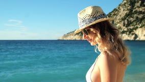 Молодая красивая девушка в шляпе и солнечных очках стоя на пляже на заходе солнца сток-видео