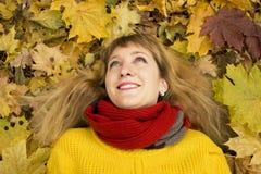 Молодая красивая девушка лежа на листьях и усмехаться осени Стоковая Фотография RF