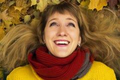 Молодая красивая девушка лежа на листьях и усмехаться осени Стоковые Изображения RF