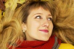 Молодая красивая девушка лежа на листьях и усмехаться осени Стоковая Фотография