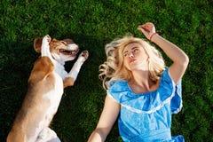 Молодая красивая девушка лежа с собакой бигля на траве в парке Стоковые Изображения RF