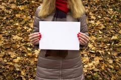 Молодая красивая девушка держа белый лист бумаги в ее руках в парке Стоковые Изображения RF