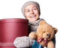 Молодая красивая девушка держа плюшевый медвежонка и коробку белой предпосылки Стоковые Изображения