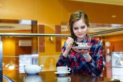 Молодая красивая девушка есть торт в кафе Стоковое Изображение