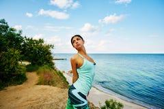 Молодая красивая девушка делая тренировки на пляже Стоковая Фотография