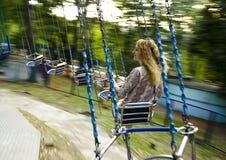 Молодая красивая девушка едет на качании приостанавливанном на цепях Стоковая Фотография