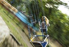 Молодая красивая девушка едет на качании приостанавливанном на цепях Стоковые Изображения RF