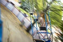 Молодая красивая девушка едет на качании приостанавливанном на цепях Стоковое Фото