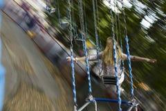 Молодая красивая девушка едет на качании приостанавливанном на цепях Стоковая Фотография RF