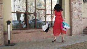 Молодая красивая девушка идет вниз с улицы города с хозяйственными сумками после успешных покупок Брюнет в платье акции видеоматериалы