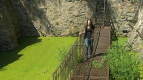 Молодая красивая девушка идет на тонкий загубленный ржавый мост металла над зеленой водой сток-видео