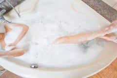 Молодая красивая девушка поливая в ванне Стоковые Фото