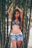 Молодая красивая девушка представляя с деревьями bamoo, горячая концепция моды лета Стоковые Фото