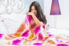 Молодая красивая девушка сидя на кровати стоковые изображения
