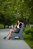 Молодая красивая девушка сидя на стенде в парке Стоковая Фотография