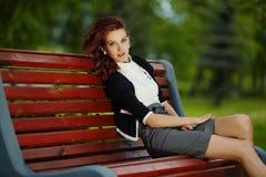 Молодая красивая девушка сидя на стенде в парке Стоковое Изображение RF