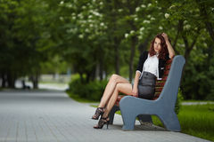 Молодая красивая девушка сидя на стенде в парке Стоковые Фотографии RF
