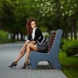 Молодая красивая девушка сидя на стенде в парке Стоковая Фотография RF