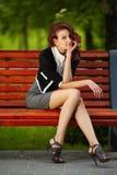 Молодая красивая девушка сидя на стенде в парке Стоковое фото RF