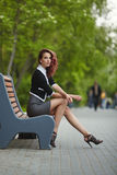 Молодая красивая девушка сидя на стенде в парке Стоковое Изображение