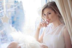 Молодая красивая девушка сидя на windowsill, смотря вне окно, свет утра, слепимость стоковое изображение