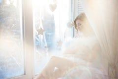Молодая красивая девушка сидя на windowsill, смотря вне окно, свет утра, слепимость стоковые фотографии rf