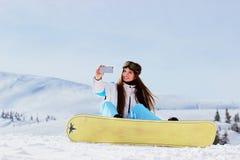 Молодая красивая девушка сноубординга с гуглит на ее головном принимая selfie с сноубордом в снежных горах Стоковая Фотография RF