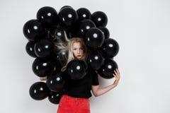 Молодая красивая девушка стоя в черных baloons над белой стеной Стоковое Фото