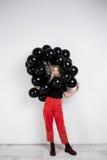 Молодая красивая девушка стоя в черных baloons над белой стеной Стоковая Фотография