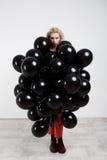 Молодая красивая девушка стоя в черных baloons над белой стеной Стоковые Фотографии RF