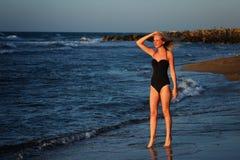 Молодая красивая девушка стоя на пляже в черном купальнике и смотря на солнце Стоковая Фотография RF