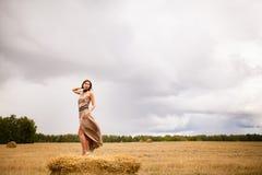 Молодая красивая девушка стоя на стоге сена Стоковые Фото