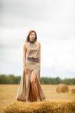 Молодая красивая девушка стоя на стоге сена Стоковая Фотография RF