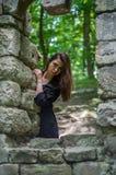 Молодая красивая девушка с длинными волосами и темным плащом смотрит вне окно старого замка от которого остались только руины в s Стоковая Фотография RF
