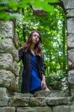 Молодая красивая девушка с длинными волосами и темным плащом смотрит вне окно старого замка от которого остались только руины в s Стоковая Фотография